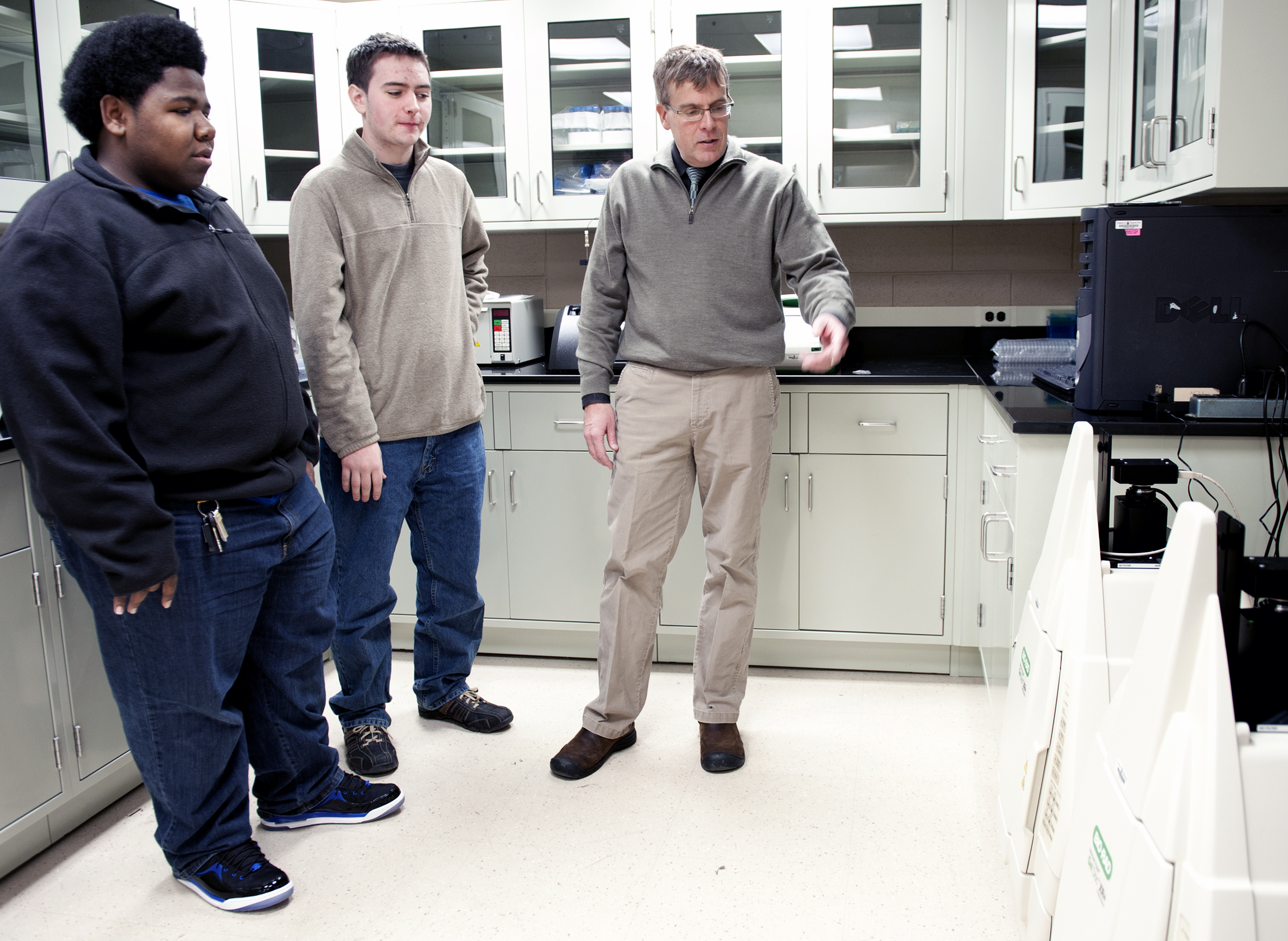 Students discuss cell culture lab equipment with a faculty member