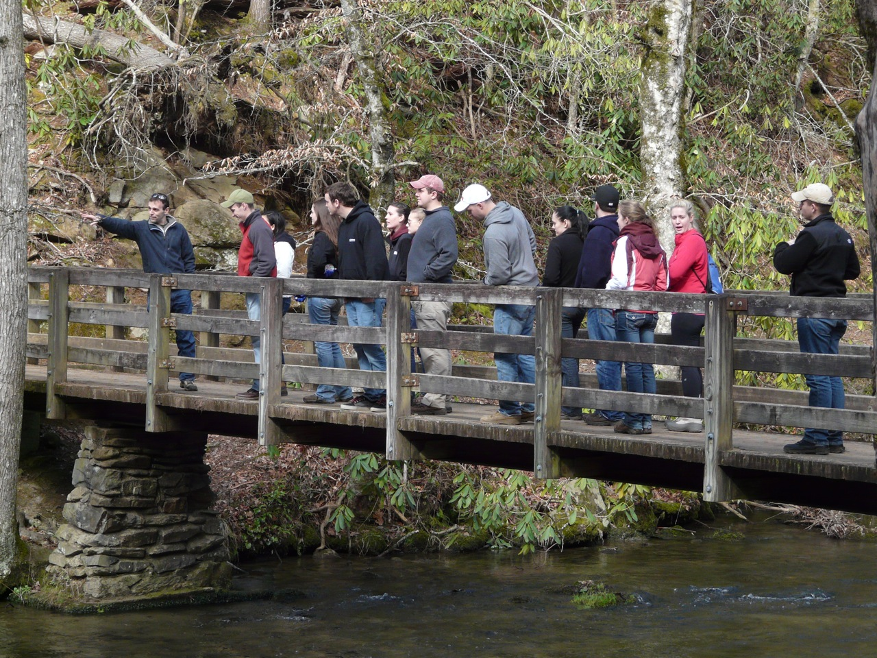 A group of people standing on a wooden footbridge over a creek.
