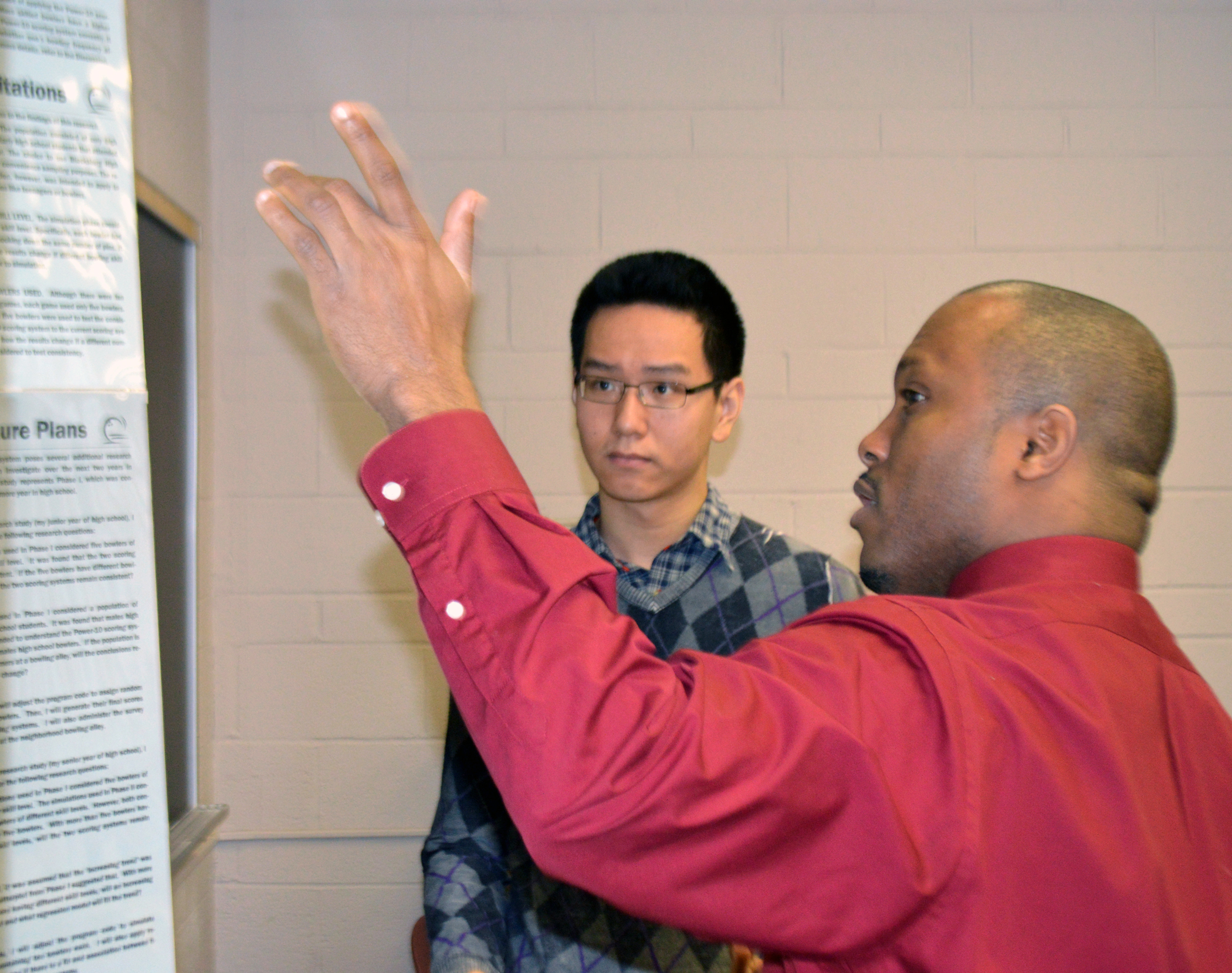 Marlow Lemons reviews a poster presentation with high school sophomore Bright Zheng