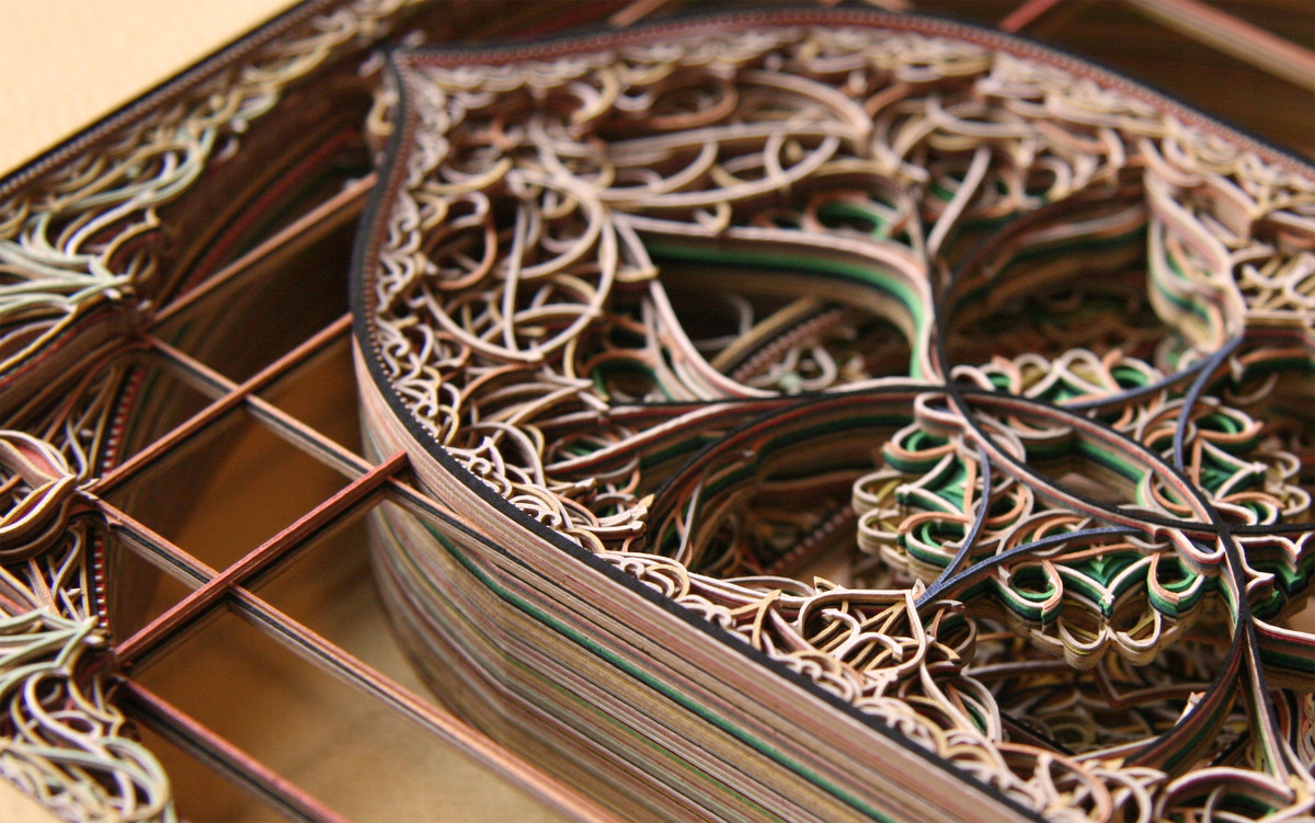 A close-up view of layers of intricately cut paper.