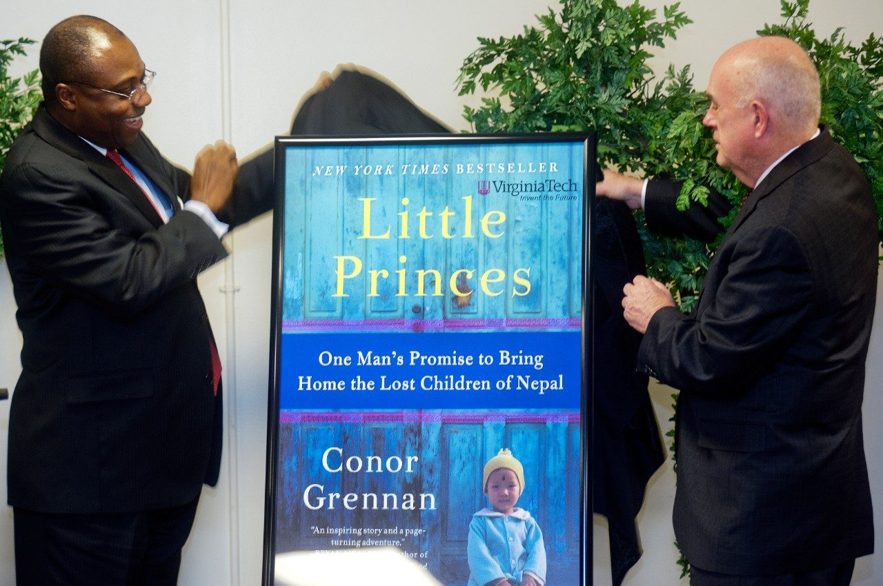"Daniel Wubah, vice president for undergraduate education, and Mark McNamee, provost, unveil ""Little Princes"" as the 2013-14 Common Book during a ceremony on Friday, March 1, 2013."