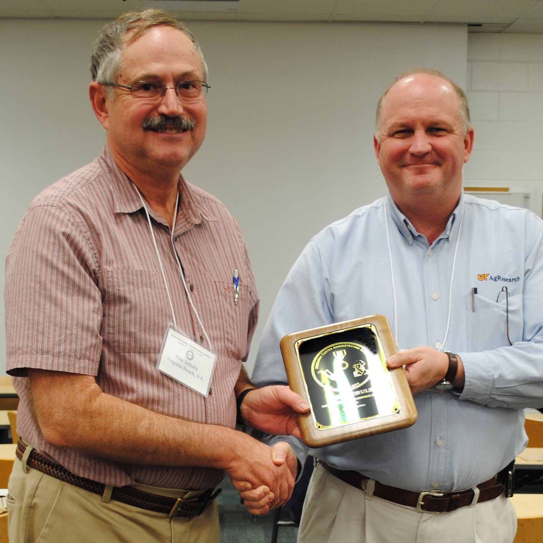 Walt Hitch presents Peter Schultz with the Distinguished Service Award from the Research Center Administrators Society of the United States.