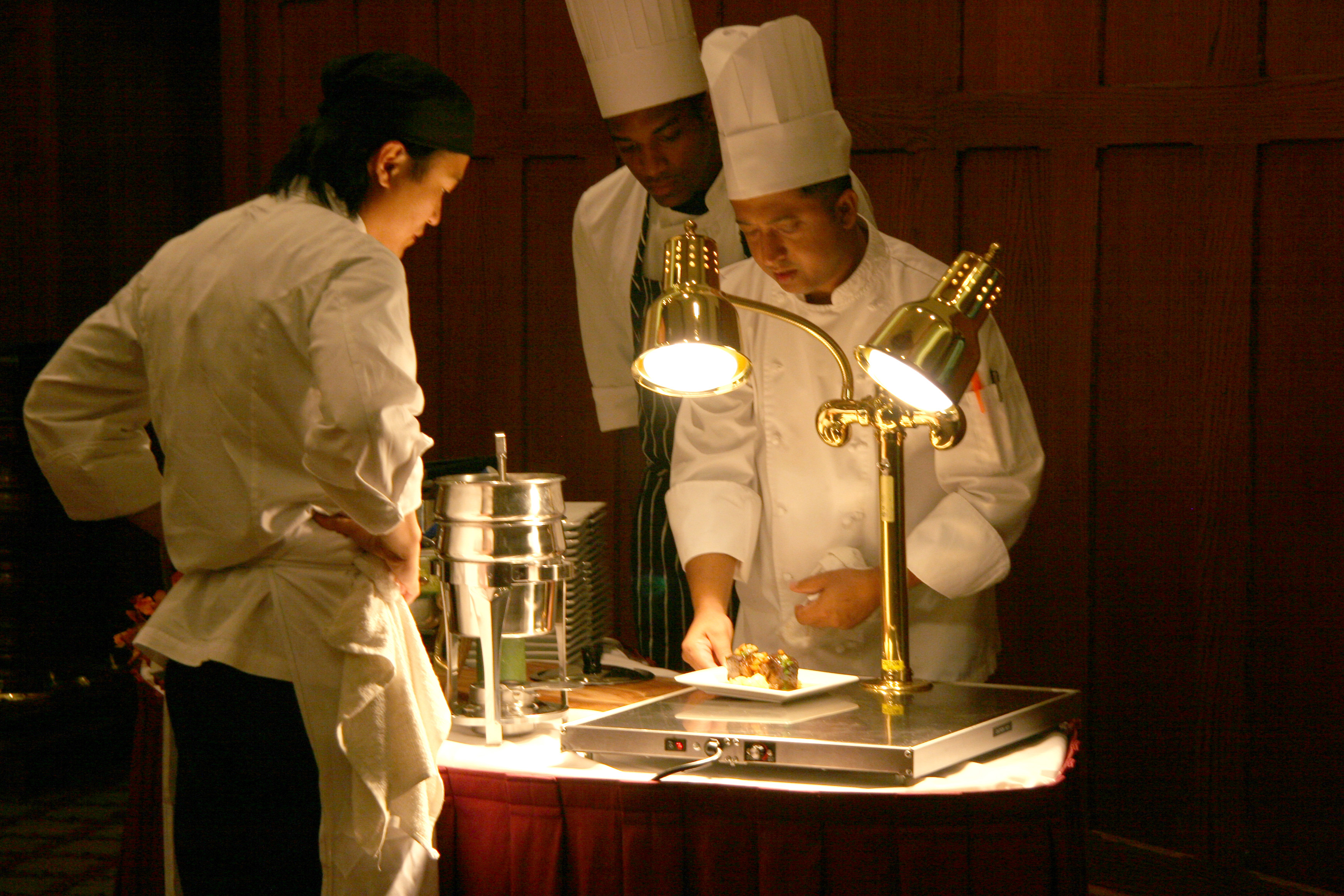 chef nazim khan mentors fellow chefs at an action station before a