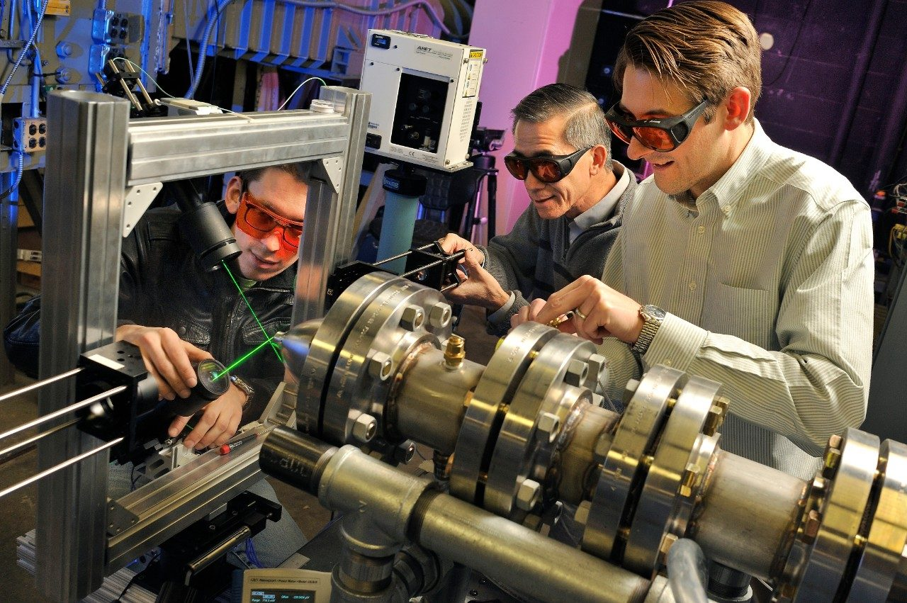 Left to right, Tobias Ecker, a doctoral student in the Virginia tech Department of Aerospace and Ocean Engineering; Wing Ng, the Chris Kraft Endowed Professor in the Department of Mechanical Engineering; and said Todd Lowe, an assistant professor in the aerospace and ocean engineering program, work on the model-scale engine inside a Randolph Hall lab.