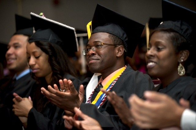 Graduating students applaud at the ceremony.
