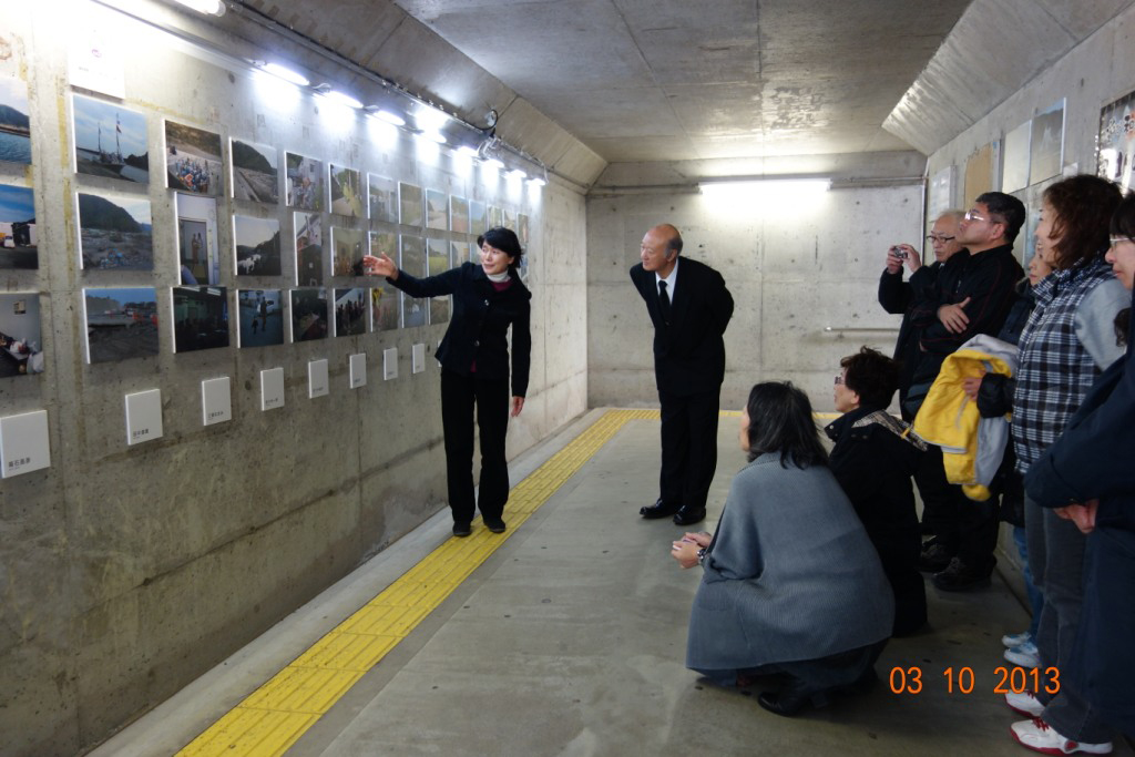 A group of Japanese people in a railway station looking at a photography exhibit on the wall.