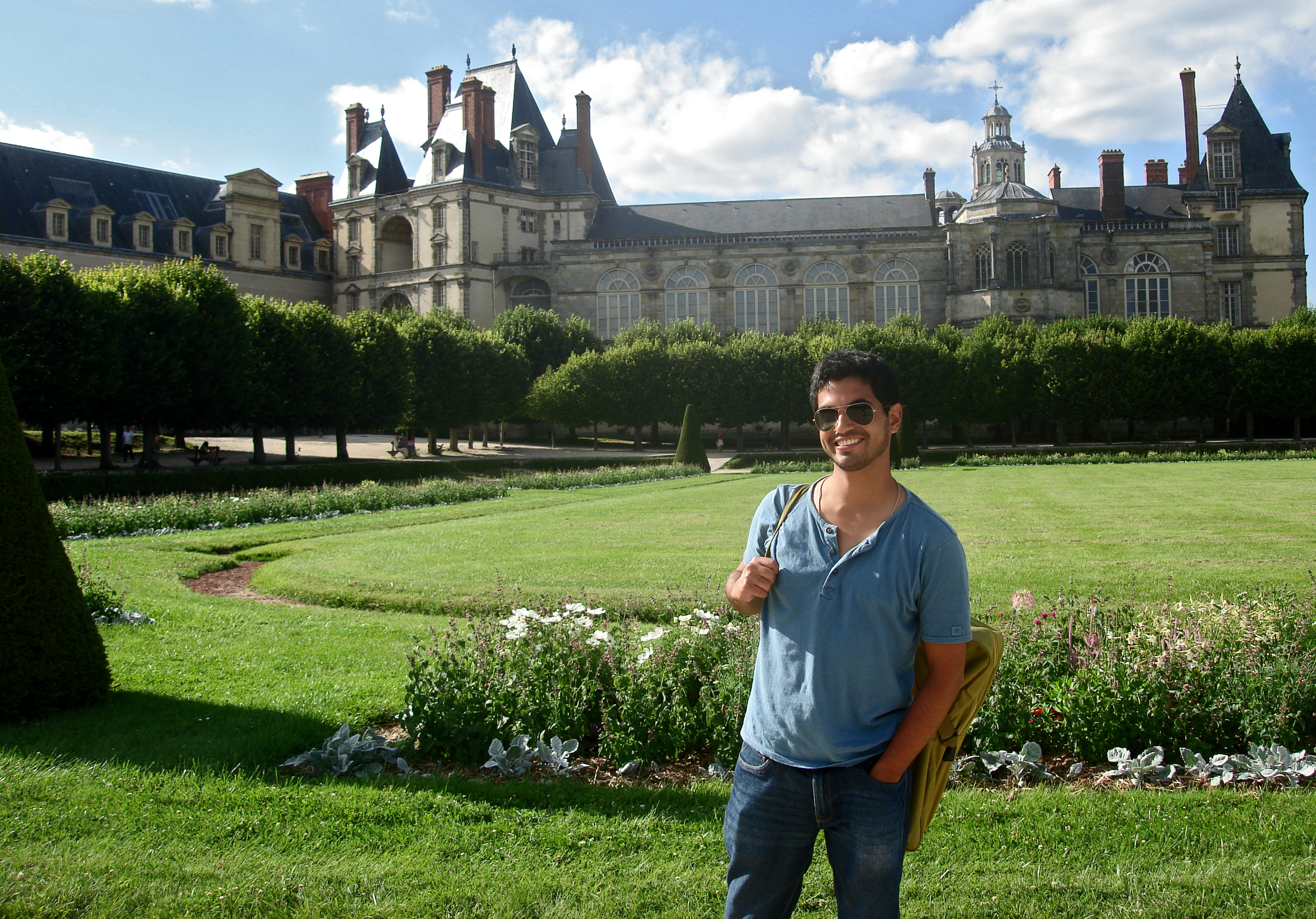 Deigo Arias-Caballero standing with the large chateau of Fontainebleau in the background.