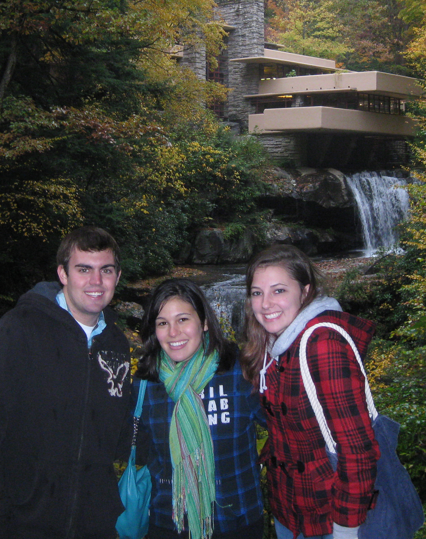 Three students stand in front of a house built over a waterfall.