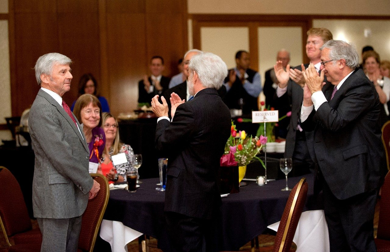 Pamplin College of Business dean Richard E. Sorensen receives a standing ovation at his retirement reception from President Charles W. Steger (far right), finance professor and department head Art Keown (center), and other guests. Sorensen's wife, Carol, is to his left.