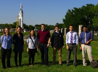 Seven students stand in front of a rocket at NASA's Johnson Space Center