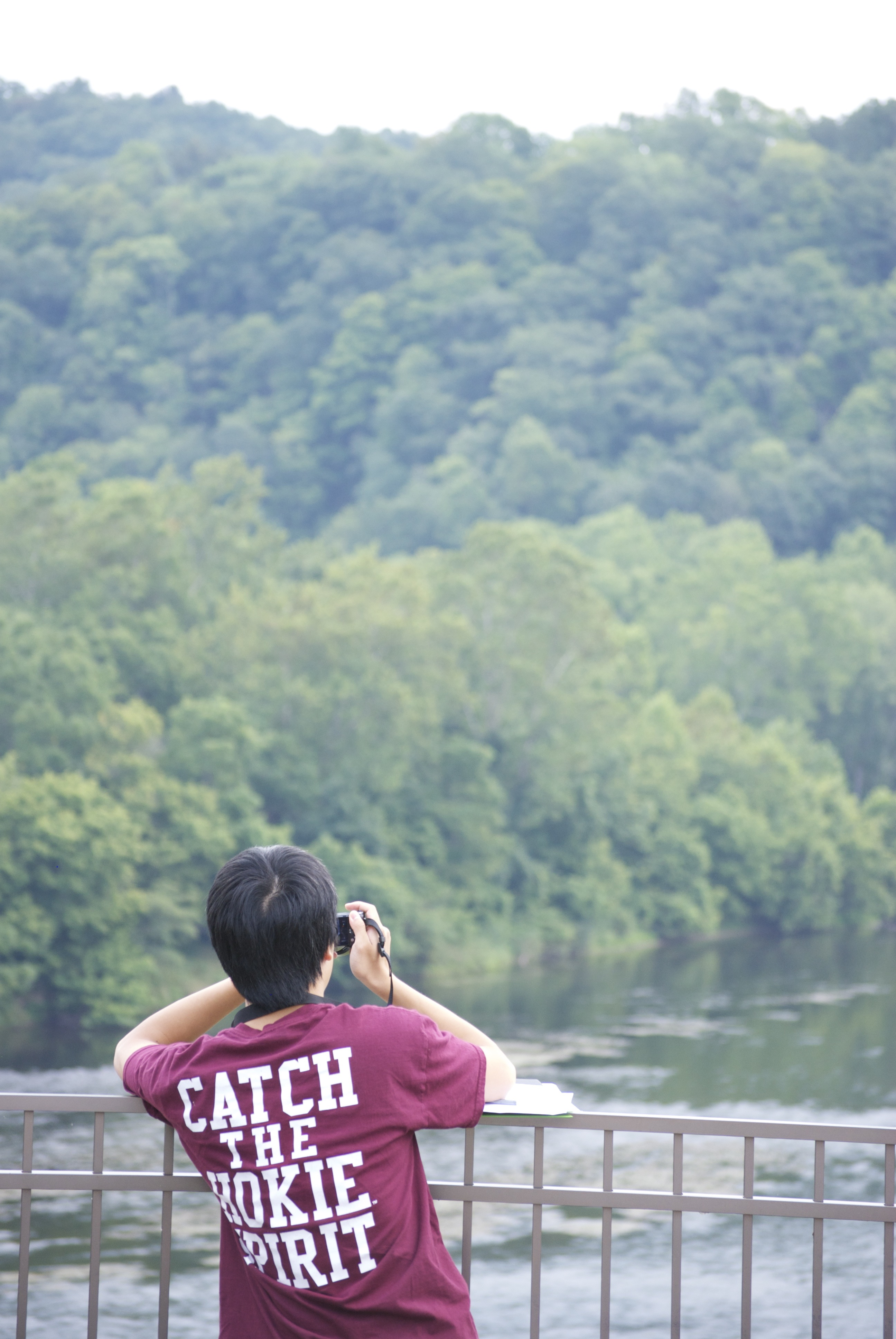Student stands on a bridge overlooking a river and takes a picture