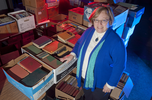 Leisa Osborne stands in a room with many boxes of books