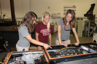 Alisha Konst, Robin Roston both rising juniors in mechanical engineering at Virginia Tech, and Alison Brown a rising sophomore in electrical engineering at Virginia Western Community College meeting at Virginia Tech's Center for Vehicle Systems and Safety (CVeSS) Lab.