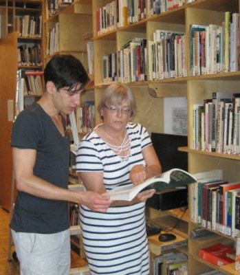 Marlene Koenig and student Nicolas Balacco looking at a book in the Virginia Tech library