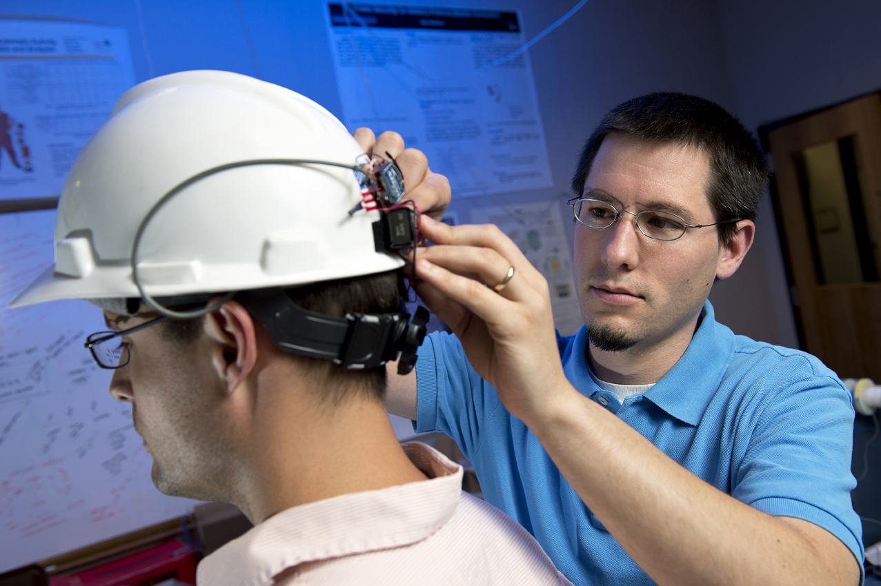 Jason B. Forsyth, right, places a wearable computing system on a helmet worn by the person on the left.