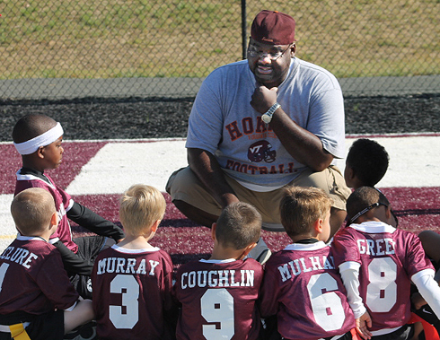 Dwight Vick talking with young football players