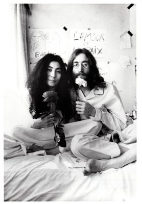 Yoko Ono and John Lennon sit in a bed holding flowers