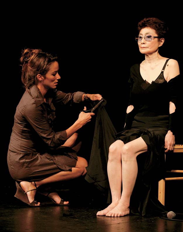 Yoko Ono sits in a chair onstage as a woman cuts her clothing.