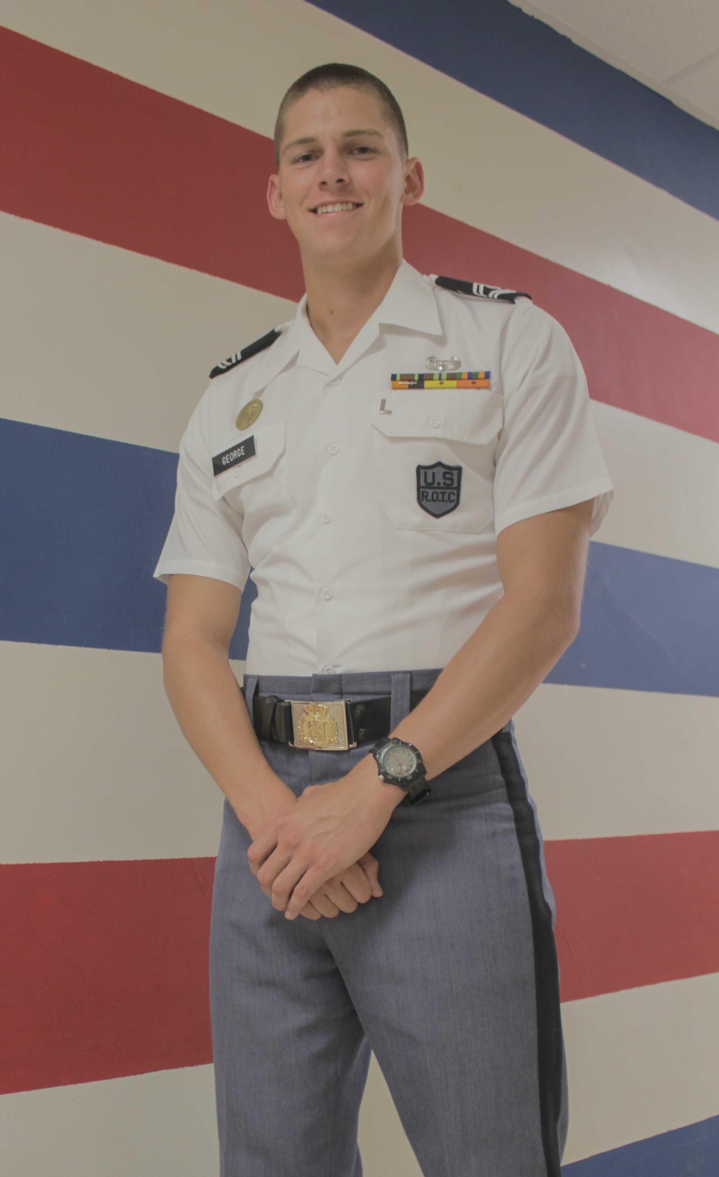 Cadet 1st Sgt. Andrew George stands in his company area against a wall painted with red, white, and blue stripes