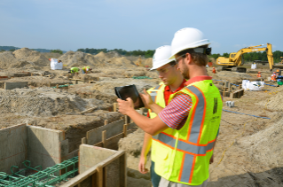 Virginia Tech students Zach Wegryn and Ryan Piplico using Autodesk BIM 360 Field software on an iPad to verify grade beam locations on site. By aligning footings using the iPad, the model shows them instantly what the building will look like through a virtual environment.