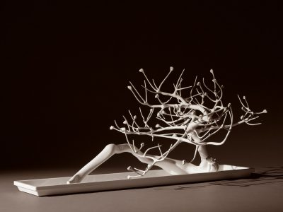 A white sculpture resembling a twisted, budding tree without leaves.