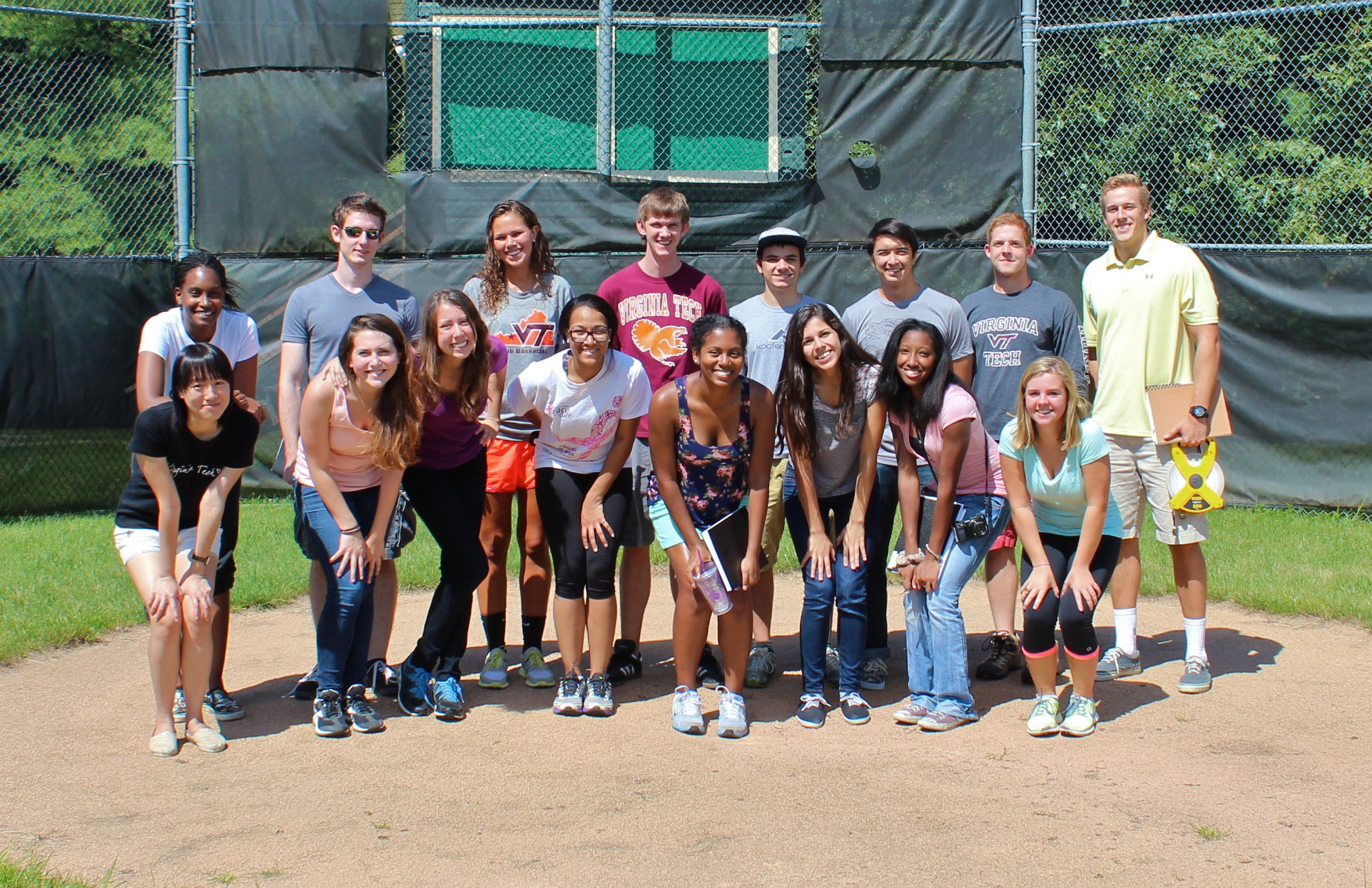 A group of 16 students stand on a baseball field.