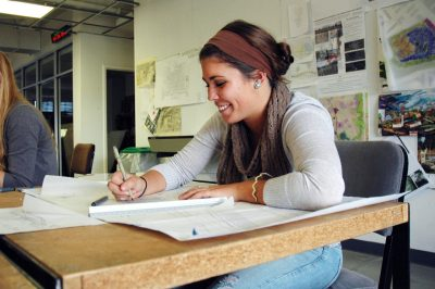 A female student using a pen to draw renderings