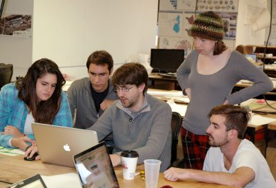 A team of five students gathers around a laptop working on their concept.