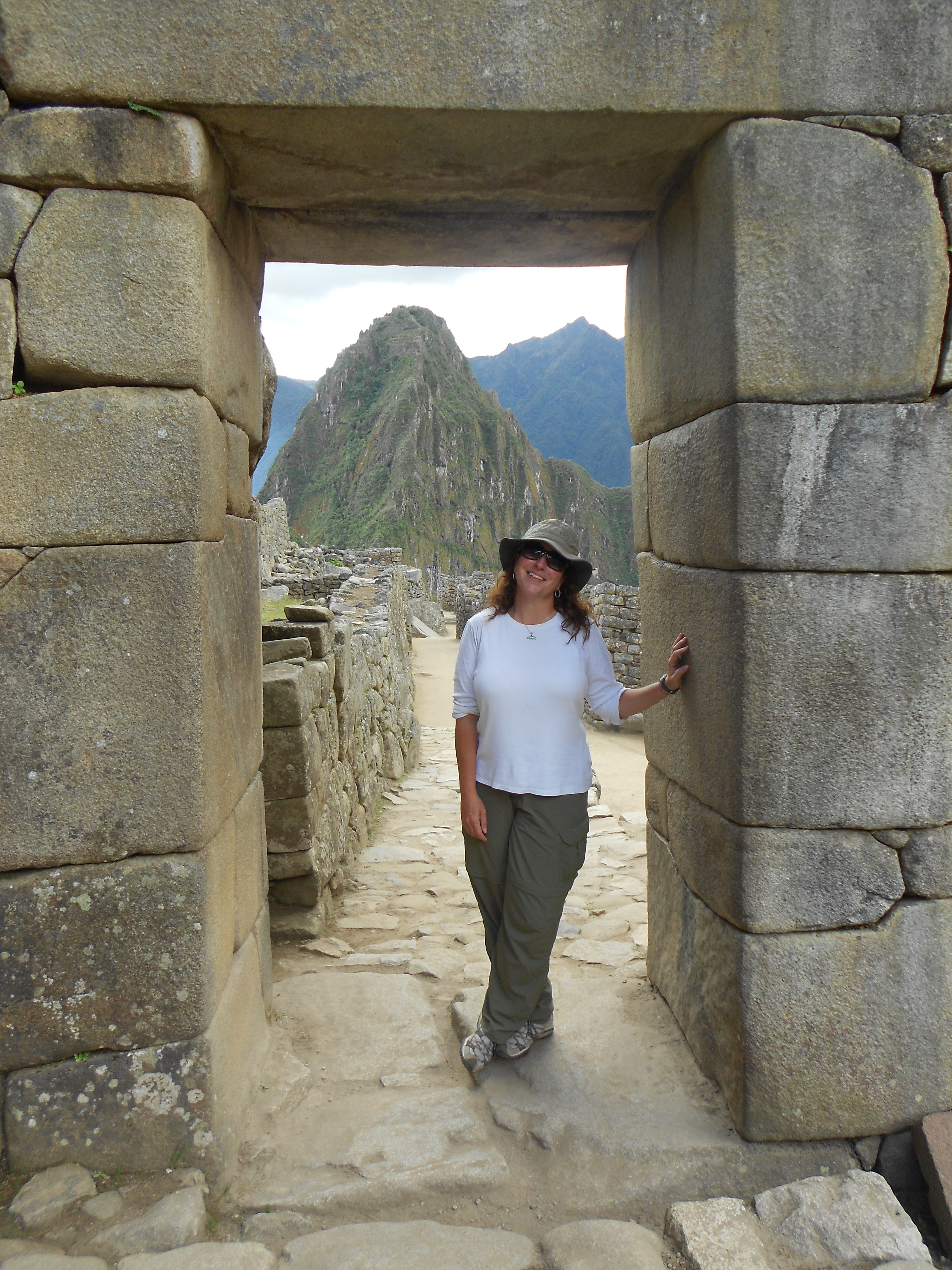 Christine Fiori stands in a stone doorway on a road leading towards the mountains at Machu Picchu.