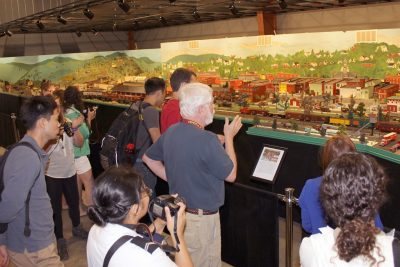 John White and students stand before a large diorama of the town of Pulaski inside the transportation museum