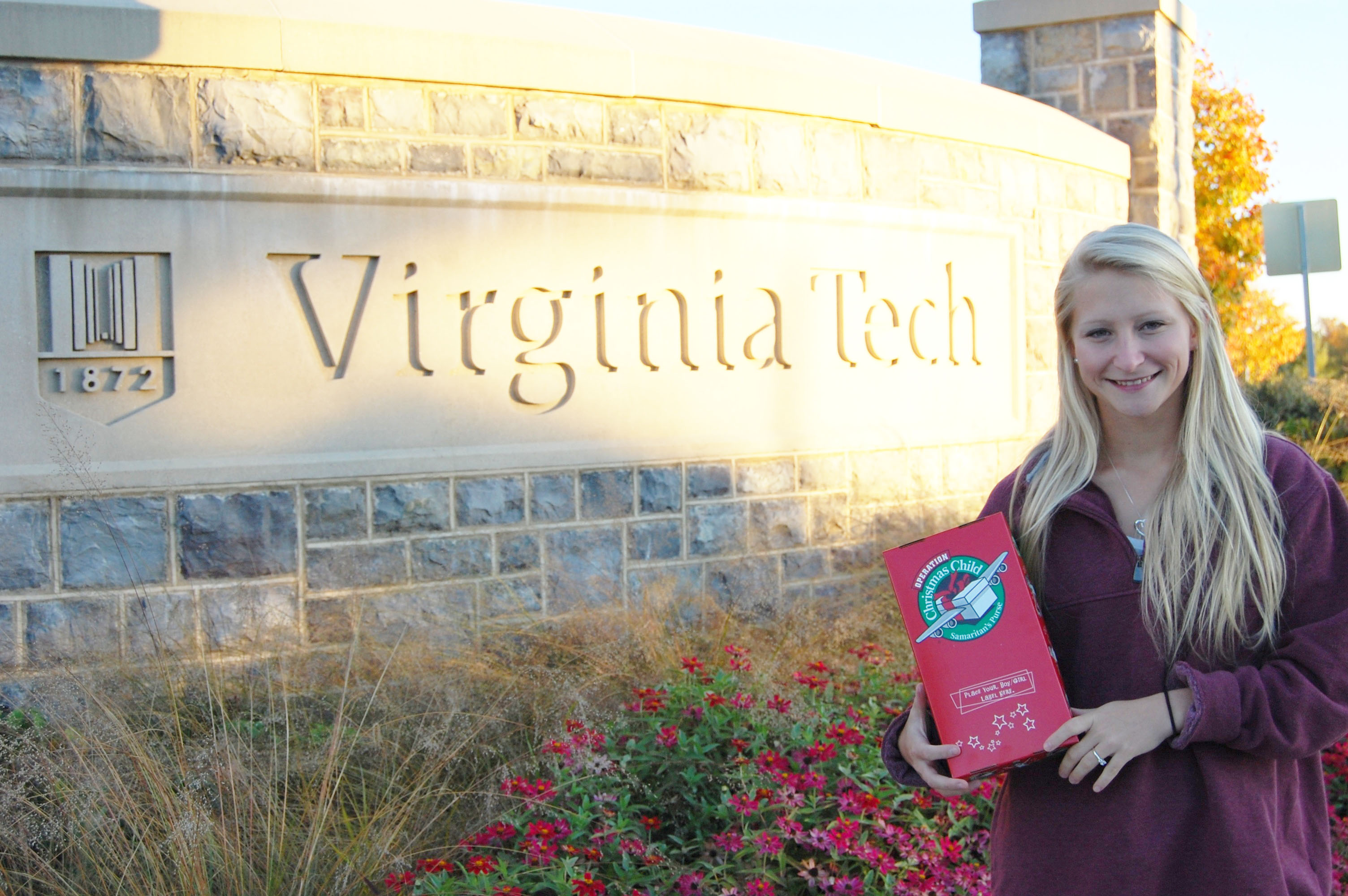 Student stands in front of Virginia Tech entrance sign