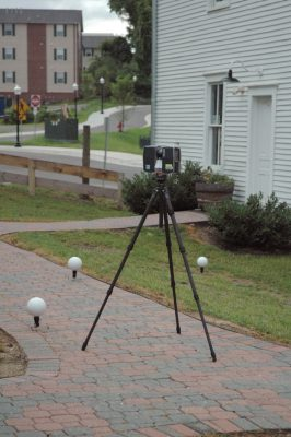 The scanner on a tripod and three spheres are positioned in front of St. Luke and Odd Fellows Hall