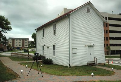 A two story white building with apartments and a parking garage in the background. In the foreground, there are three white spheres on the ground and a scanner on a tripod.