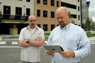 Two men stand outside looking at an iPad.