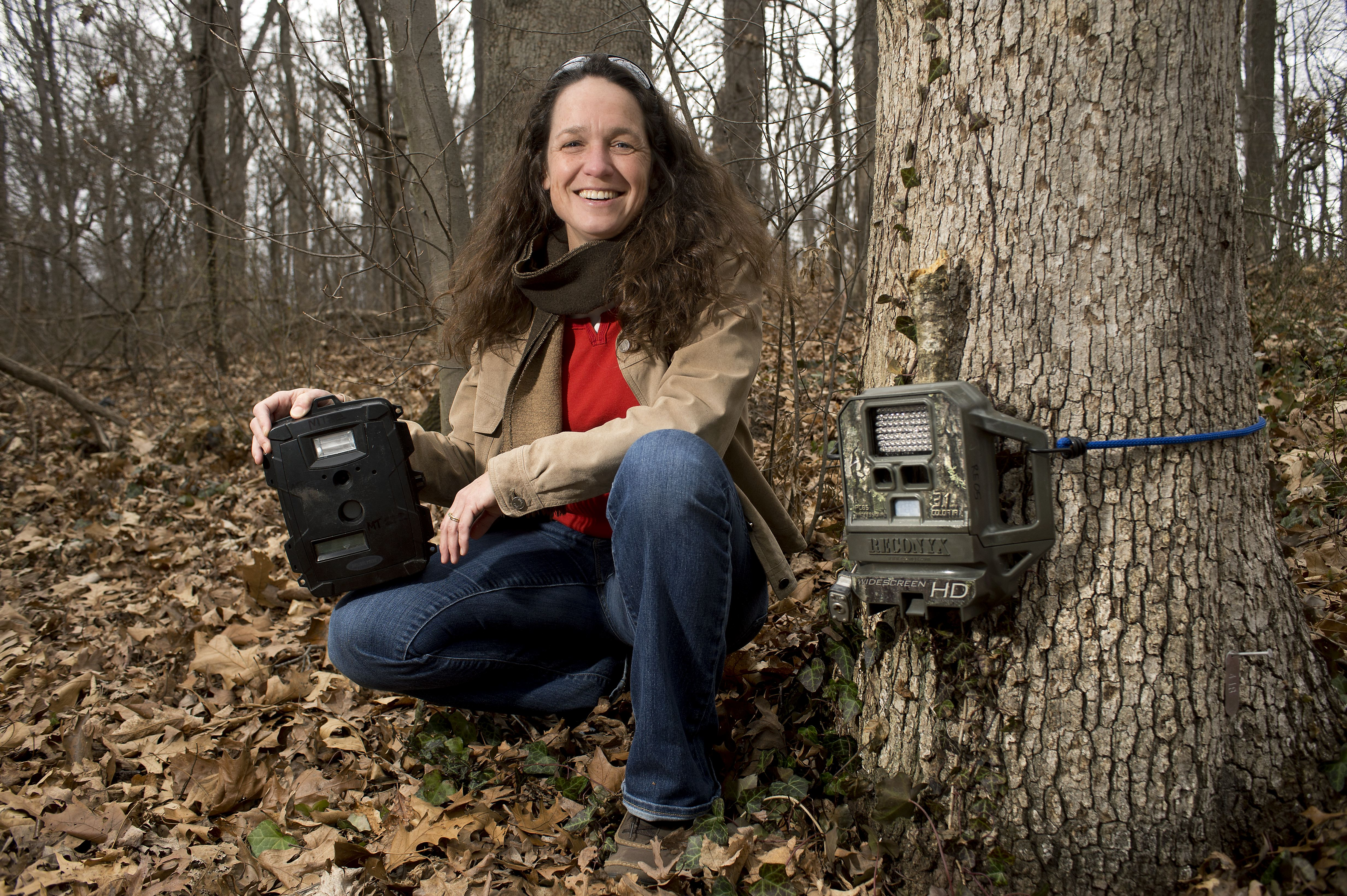 Marcella Kelly in the woods with a camera trap