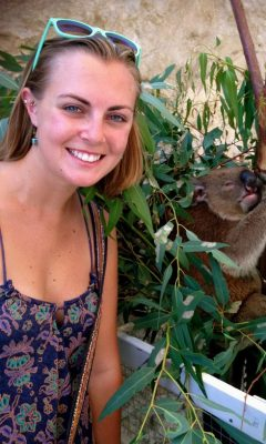 Paige McKinley next to a koala in a tree.