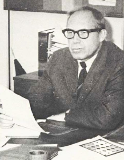 An old black an white photo of Charles Burchard working at a desk