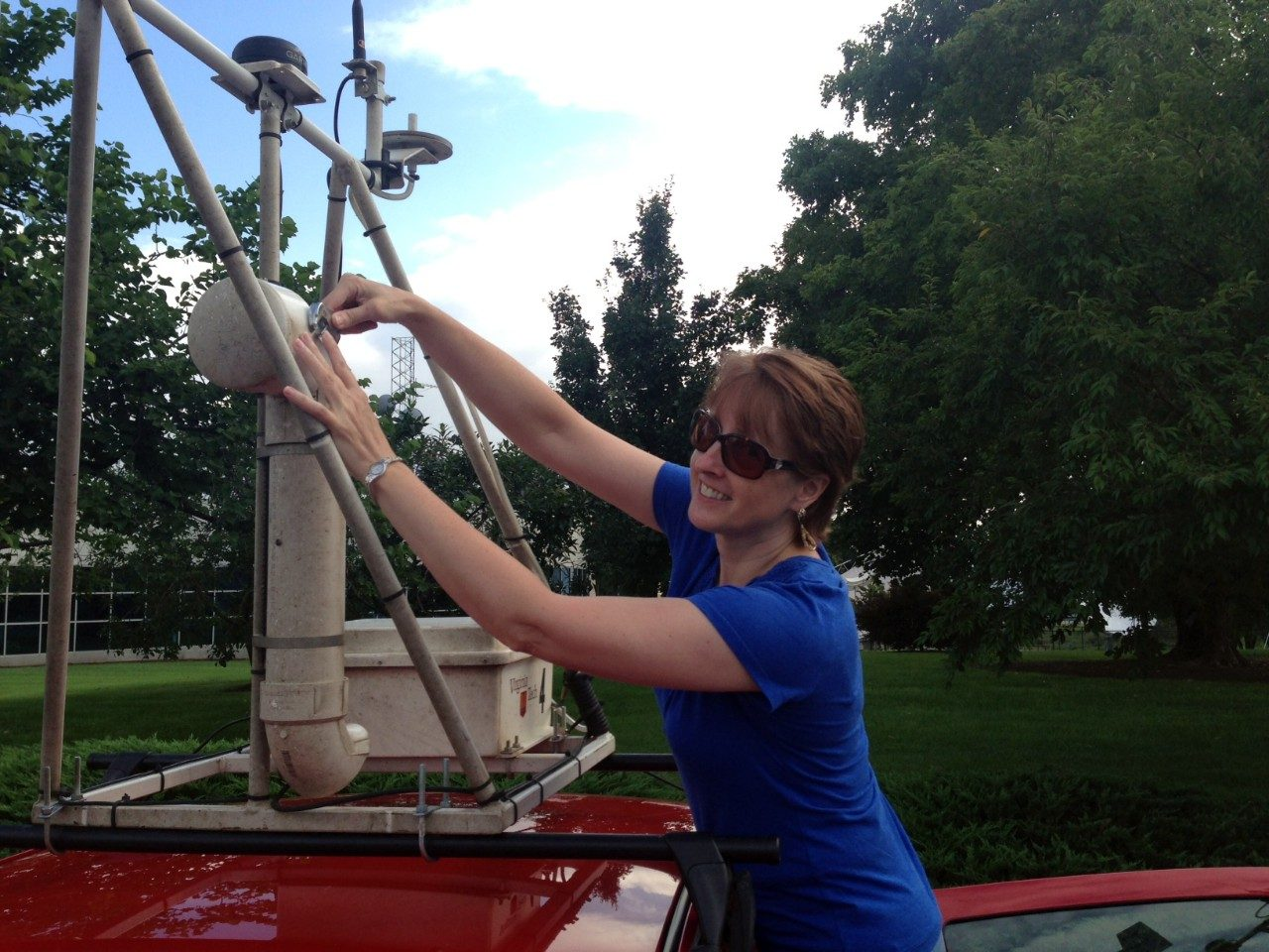 Tammy Parece helps mount one of Virginia Tech's mobile weather units on top of a vehicle to collect data for her research.