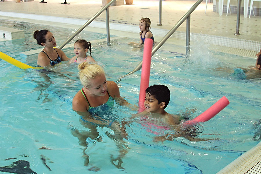 Swim instructors helping young people learn to swim