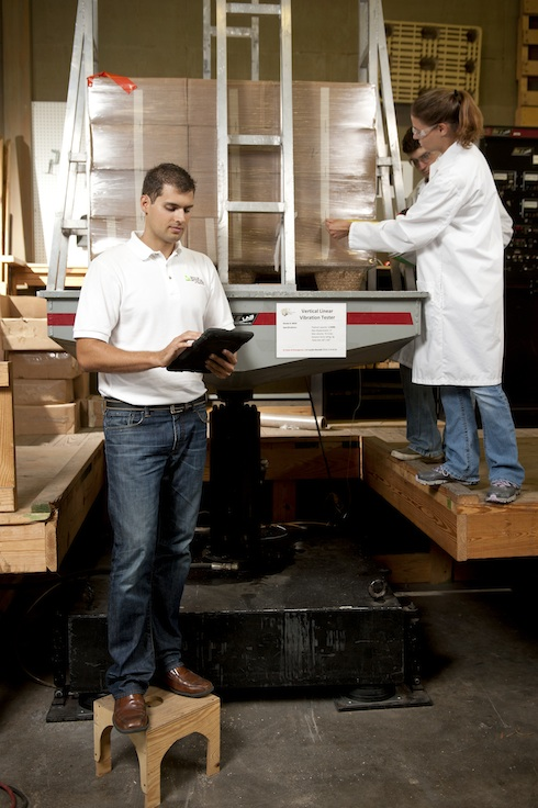 A man enters information into a tablet while two students measure a plastic-wrapped load on a pallet.