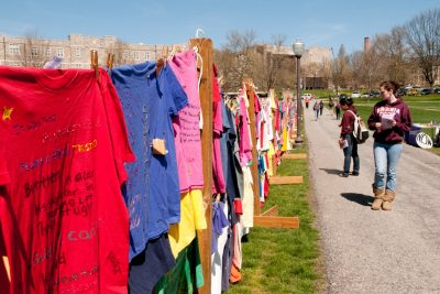 Individuals who have been impacted by violence against women, either themselves or a friend or family member, create shirts to go on display as part of the Clothesline Project. The different colors represent different types of violence.