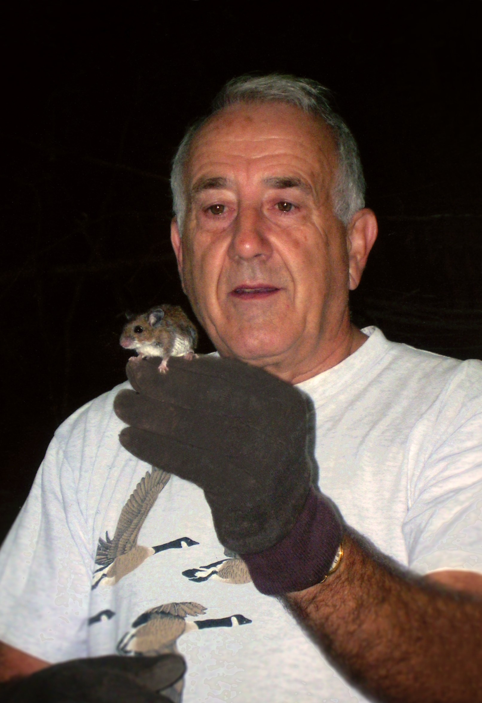 Donald Linzey in the woods holding a deer mouse