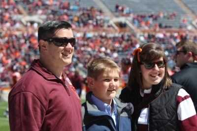 Erin Helbling, right, and her brothers Jacob and Caleb, left to right, enjoyed the presentation of the Family of the Year award at the spring football game.