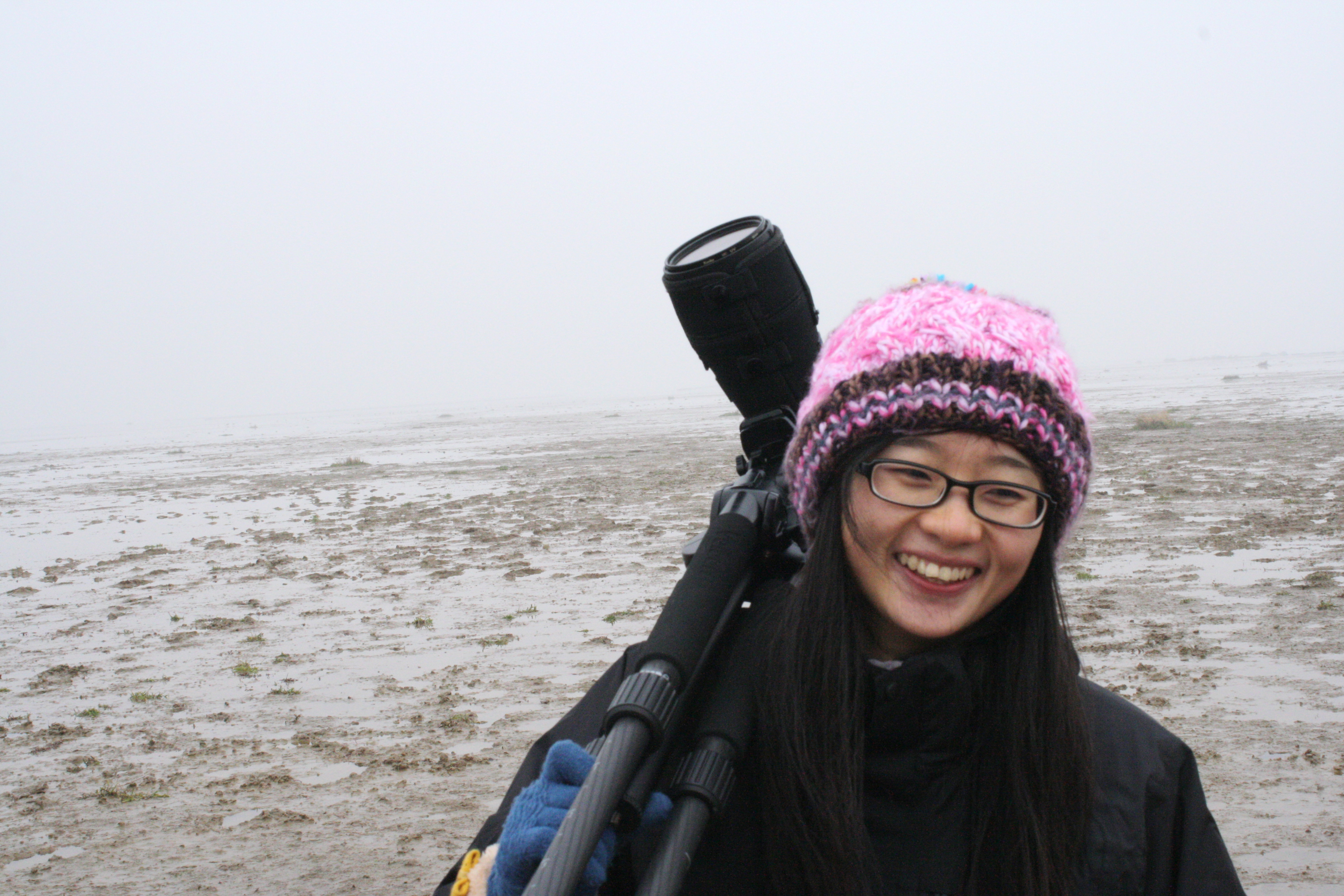 A woman holding a spotting scope stands on a mud flat