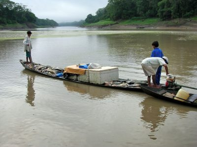 A small wooden boat loaded with fish on a river, with three people aboard
