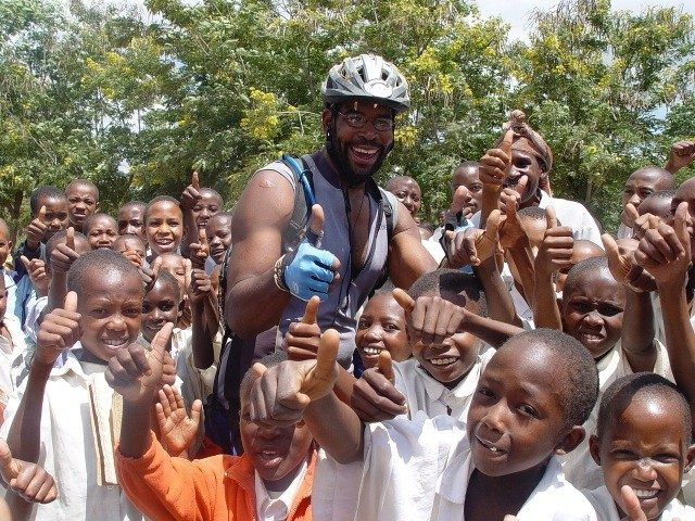 David Sylvester poses with some children during his transcontinental cycling trip across Africa.