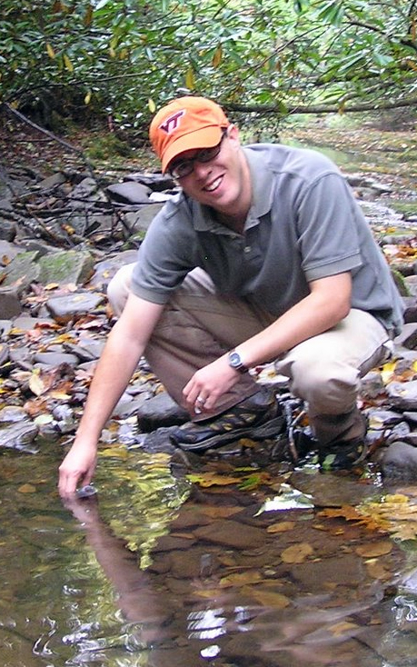 Kevin McGuire takes a water sample in a forest stream