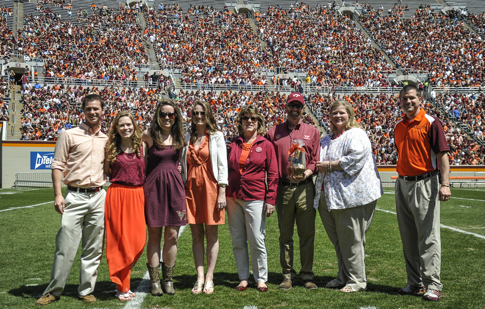 Thomas Clements; Heather Hicks; Mikayla Meyer; Amanda Clements; Faith Hicks; Alan Hicks; Patty Perillo, vice president of Student Affairs; and Rick Sparks, associate dean, New Student and Family Programs stand on the football field