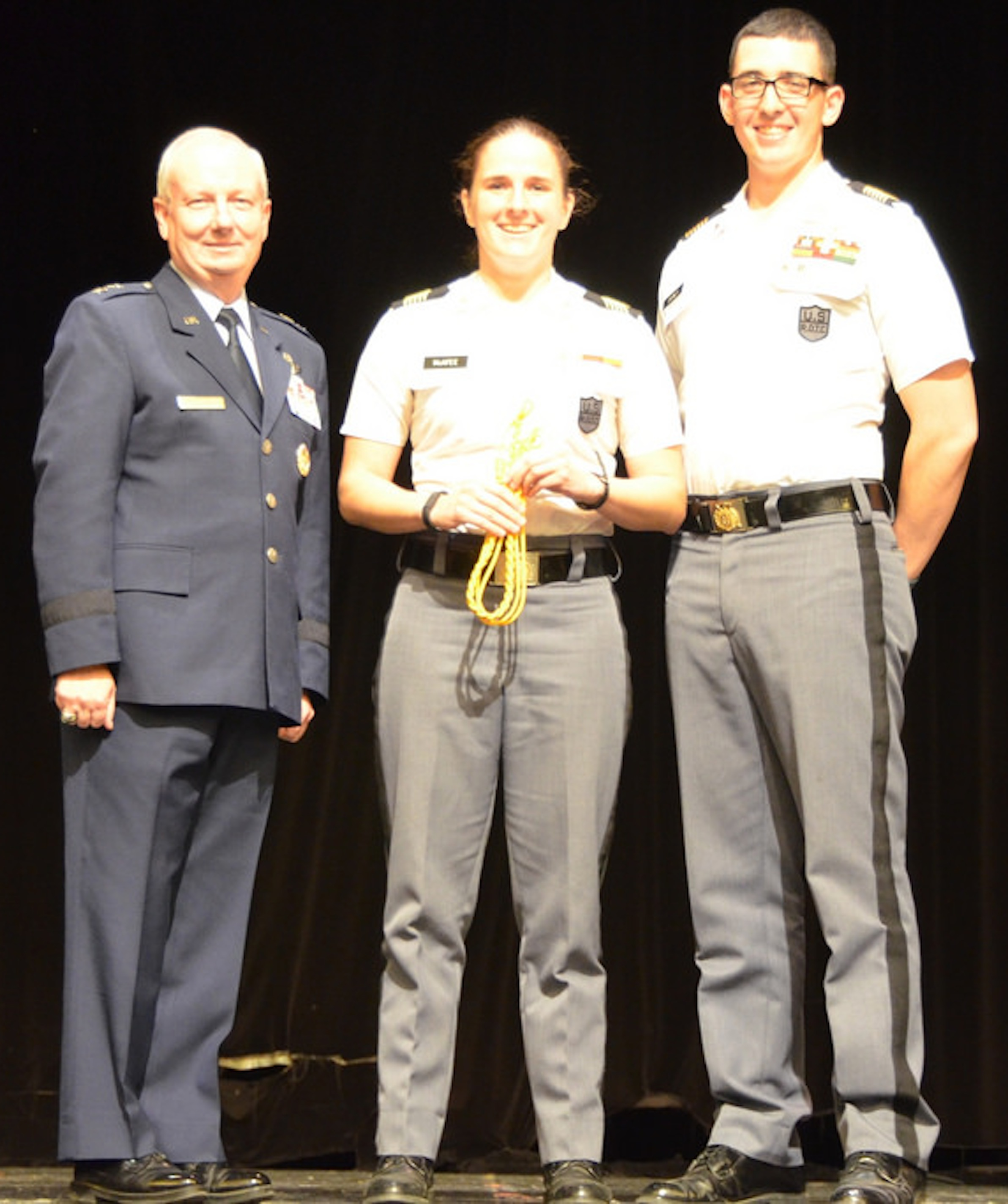 Cadet Rebecca McAfee, center, Hotel Company commander, accepts the Gold Cord from the Commandant of Cadets Maj. Gen. Randal Fullhart, left, and the Regimental Commander Cadet Jordan Disney, right.