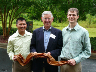 (Left to right): Nhiem Cao, Wolfgang Glasser, and Kevin Oden hold a streamer of biodegradable plastic made by cycleWood Solutions Inc.